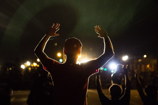 Demonstrators hold up their hands outside the burned and looted Quik Trip gas station Tuesday August 13, 2014 in Ferguson, Missouri. | Jessica Koscielniak / Chicago Sun-Times